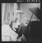A group around a piano in the main lounge at Idaho Hall, Arlington Farms