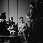 Residents chat in a lounge outside the laundry room.